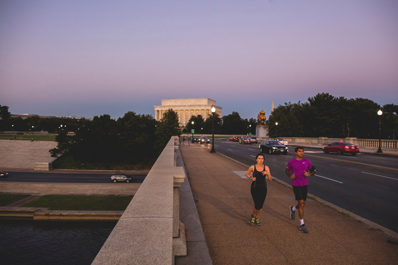 Couple running by the Lincoln Memorial in warm weather - Outdoor activities and fitness in Washington, DC