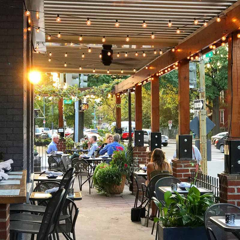 Diners at Tyber Creek Wine Bar and Kitchen on the outdoor patio - Where to eat and drink in Washington, DC's Bloomingdale neighborhood