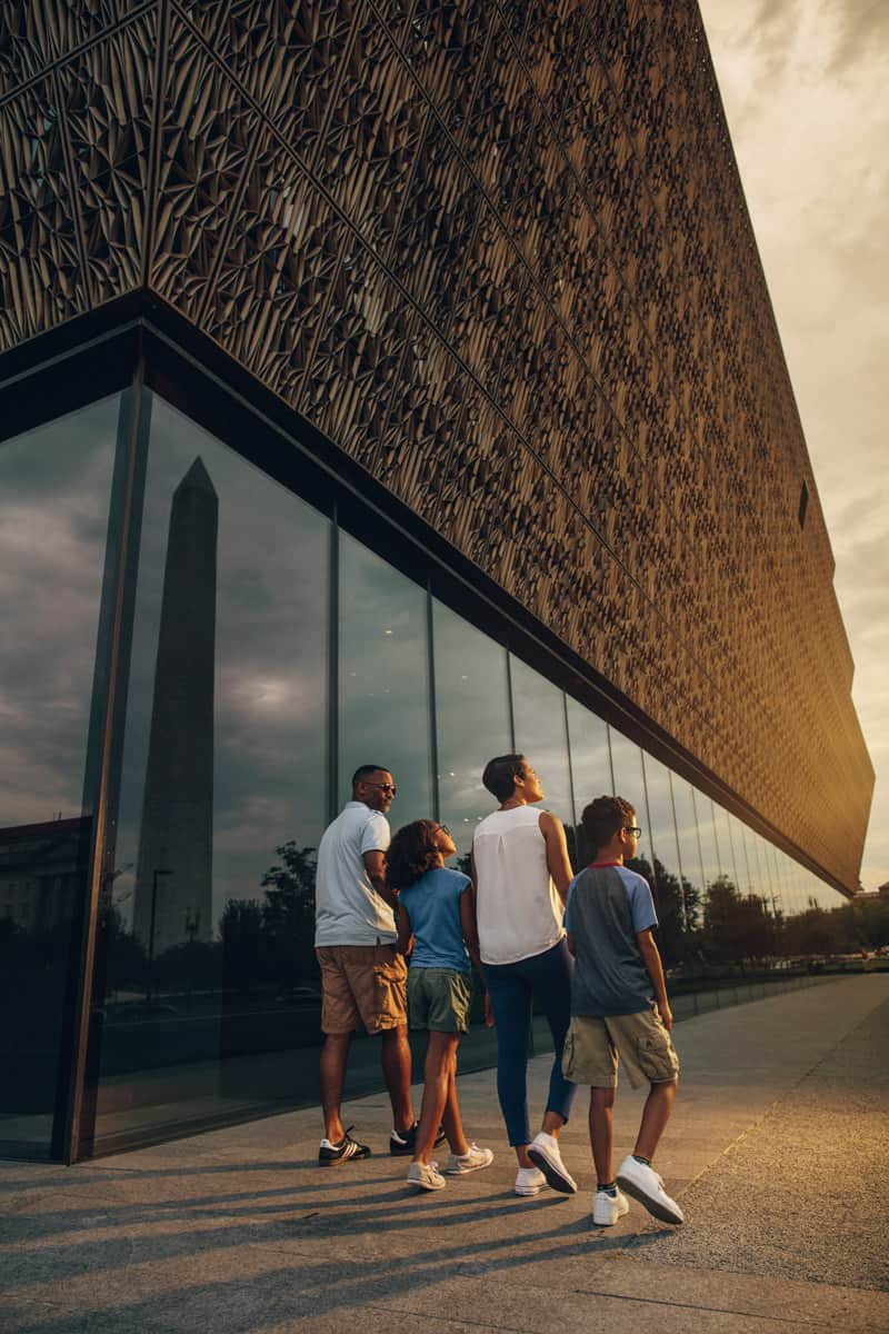 Family walking by the Smithsonian National Museum of African American History and Culture - Free museum on the National Mall in DC