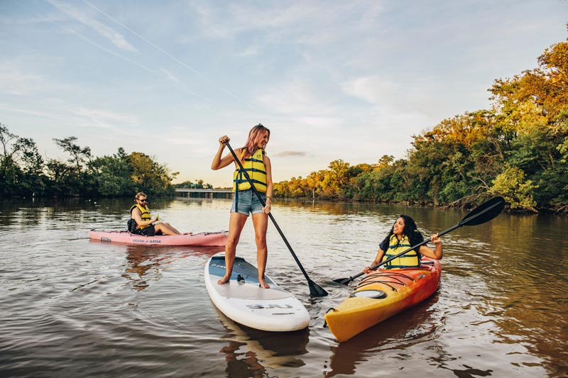 Friends kayaking and paddling on the Anacostia River at sunset - The best things to do this spring and summer in Washington, DC