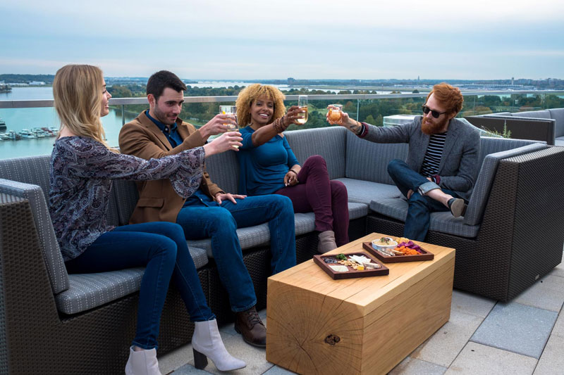 Group of friends at Whiskey Charlie rooftop bar on The Wharf - The best rooftop bars and restaurants in Washington, DC