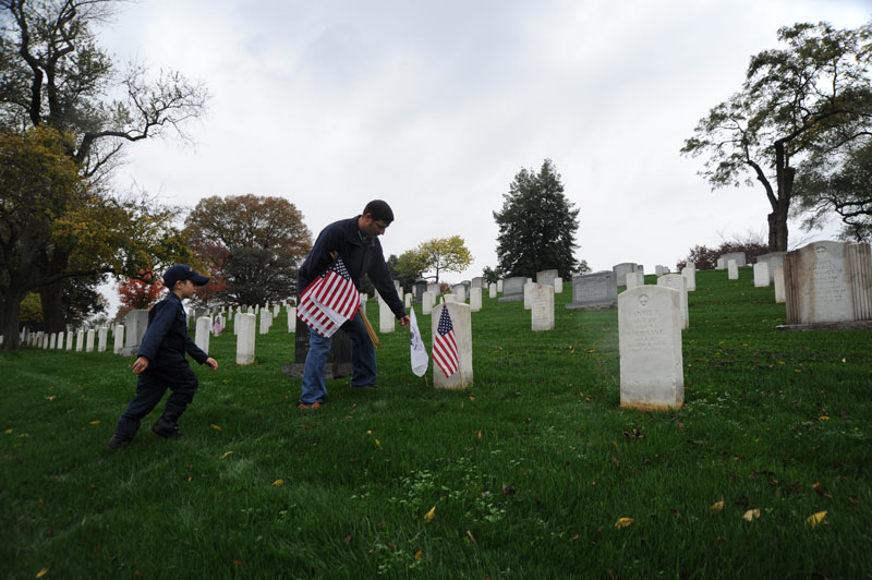 Father with child laying flags before Veterans Day at Arlington National Cemetery - Ways to honor veterans near Washington, DC