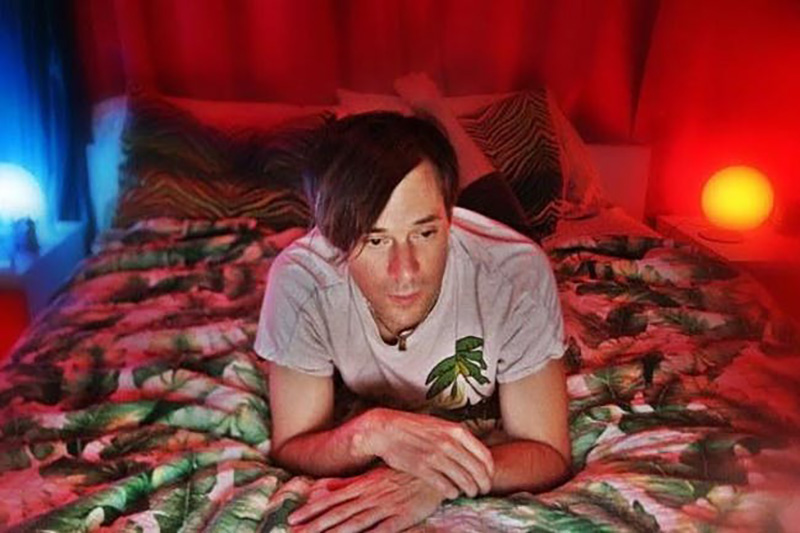Kevin Barnes of, of Montreal, laying on bed