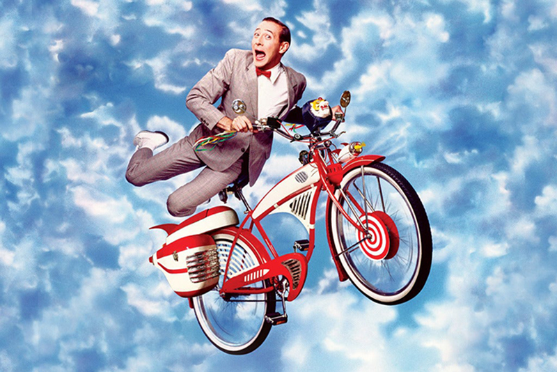 Pee-Wee Herman on a Bike making a silly face