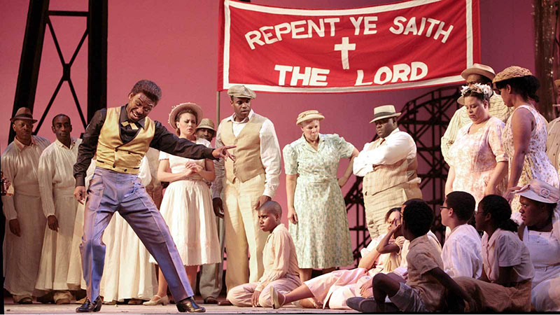 Cast of Porgy and Bess acting out in a church scene on stage