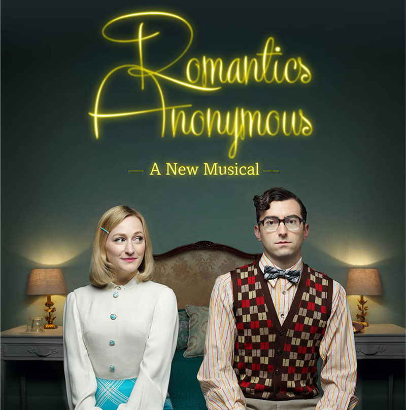 Two actors from play Romantics Anonymous Musical on bed
