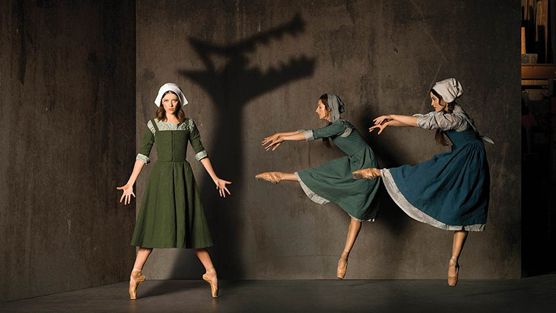 Three ballerinas on stage dressed in quaker outfits playing in The Crucible