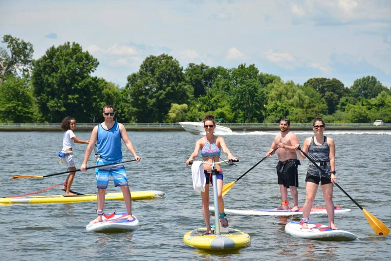 Group using paddle boards with Capital SUP DC - Eco-friendly tour options in Washington, DC