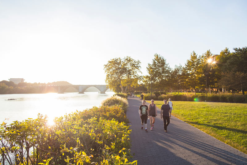 People walking along Georgetown Waterfront Park on a sunny afternoon in Washington, DC