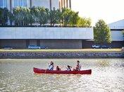 Family canoeing on Potomac River past Kennedy Center, Washington DC