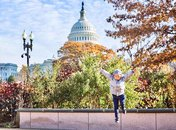 @chasingkaiphoto - Child jumping in front of the U.S. Capitol building surrounded by fall foliage - Fall in Washington, DC