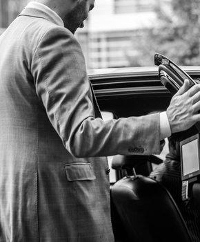 man getting inside a DC taxi cab