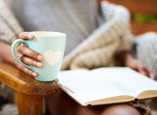 Woman holding mug and reading a book