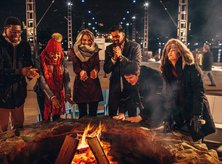 Friends gathered around the fire at The Wharf - Ways to make the most of Winter in Washington, DC