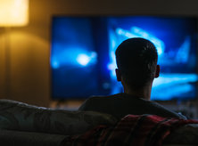 boy facing the television watching it in the dark