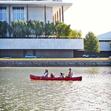 Family paddling their boat past the Kennedy Center on the Potomac River - Summer activities in Washington, DC