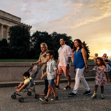 Family walking on the National Mall in front of the Lincoln Memorial during a summer evening in Washington, DC
