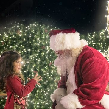 Santa Claus with child at Enchant Christmas - Dazzling holiday display, market and light maze in Washington, DC