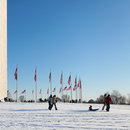 Family on snowy Washington Monument grounds on the National Mall - The best snow day activities in Washington, DC