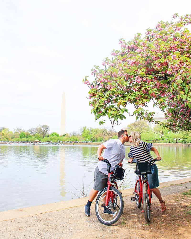 @the.snyder.spot - Husband and wife kissing on bikes in front of the Tidal Basin - Romantic places to visit in Washington, DC