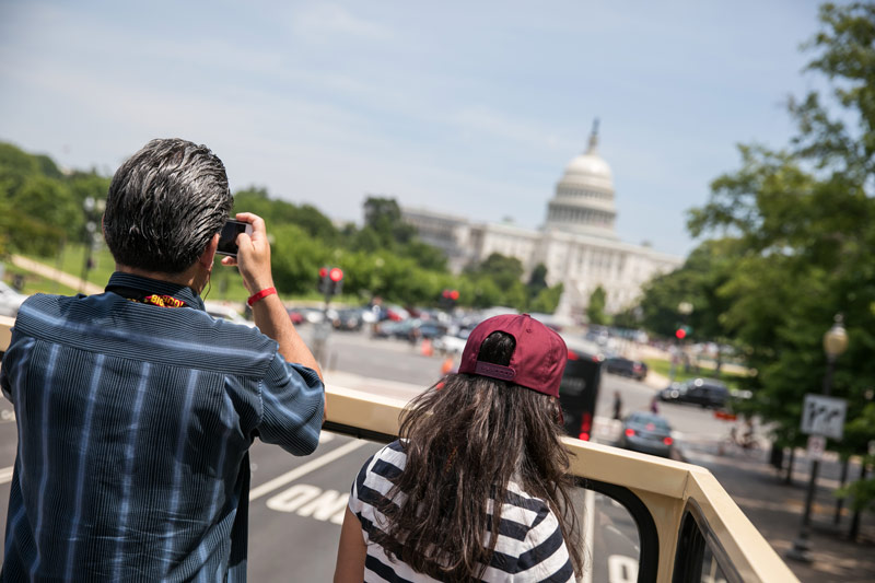 Visitors on a Big Bus sightseeing tour taking photos of the U.S. Capitol - Open-top bus tours in Washington, DC