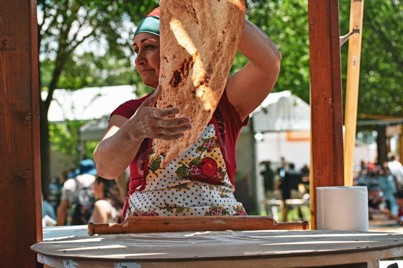 Woman making traditional bread at the Smithsonian Folklife Festival - Free summer festival on the National Mall in Washington, DC