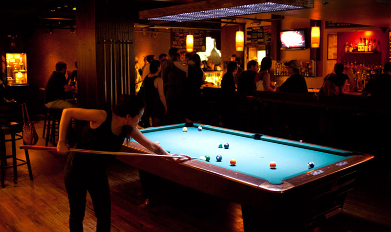 Woman playing billiards at breadsoda - Bars and restaurants where you can play ping pong in Washington, DC